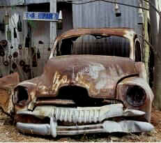 Old rusted car in old rusted tin shed